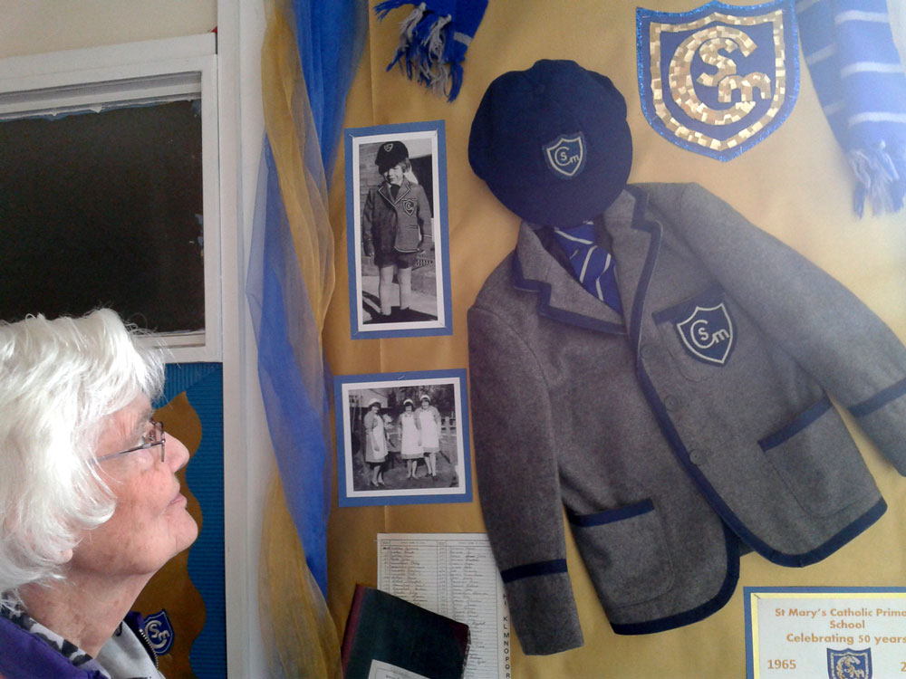 Pat Mepham looking at the old uniform and other memorabilia.  Pat son and daughter attended the school in the 1970s