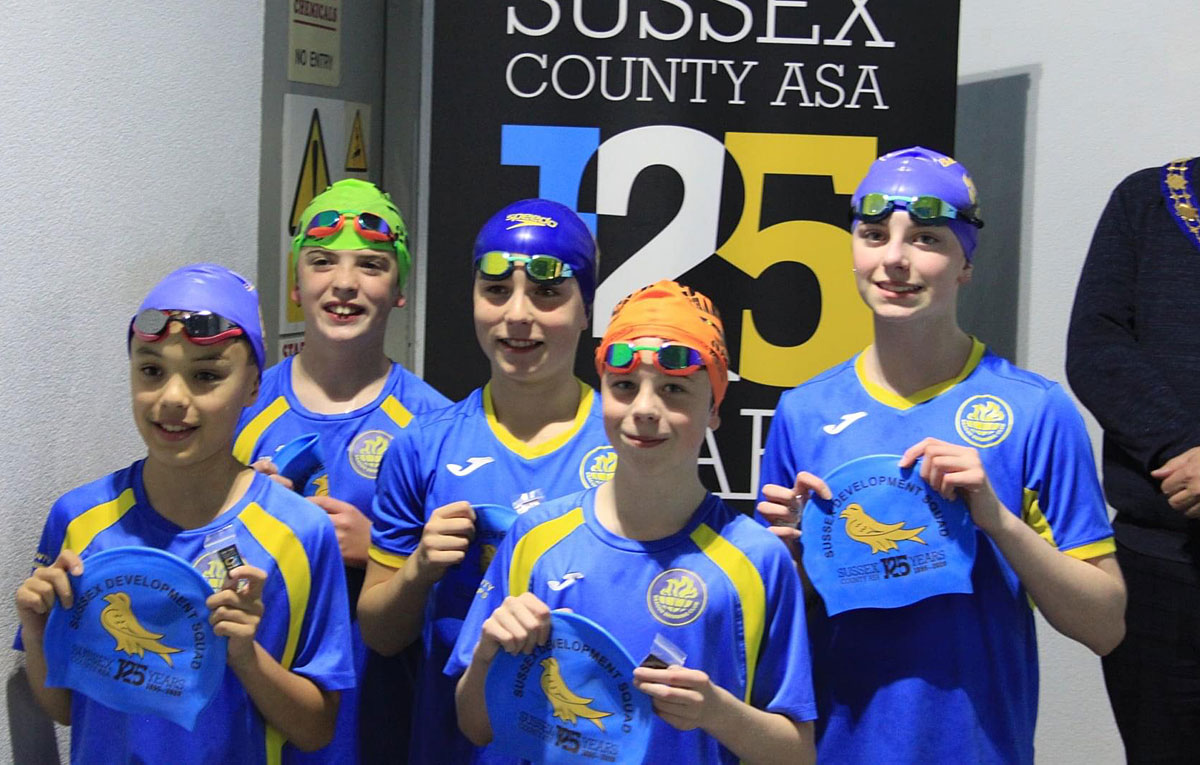 Swimmers from Beacon Swimming Club receiving their their Sussex Development Squad swimming caps